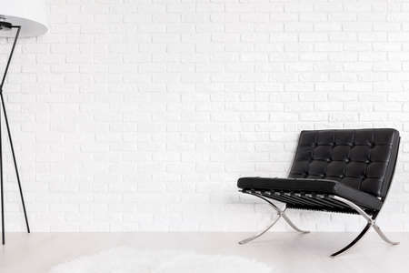 lounge chair: Black quilted lounge chair in a white interior with a brick wall