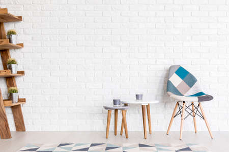 avantgarde: Modern patchwork armchair, coffee tables and ladder shelf by a white brick wall