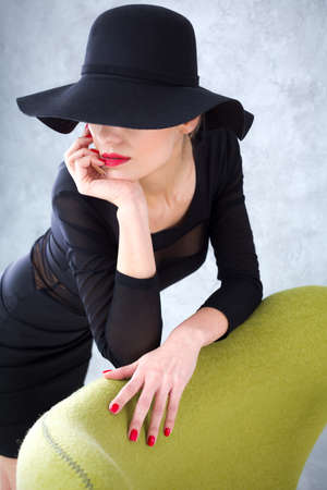 vamp: Portrait of a sexy woman in a black dress and a hat covering her eyes, resting upon a green armchair