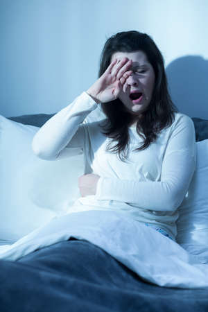 insomniac: Shot of a young woman sitting on her bed and yawning Stock Photo