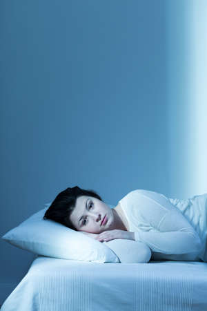 eyes open: Shot of a tired young woman laying on a bed with her eyes open Stock Photo