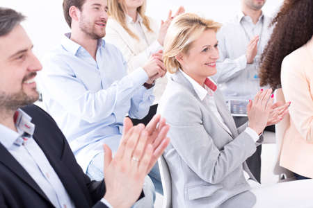 participants: Participants of the corporate meeting clapping hands and smiling, with a middle-aged woman in the centre