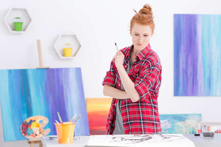 preoccupied: Shot of a red-haired artist in her atelier, preoccupied with a painting she is working on