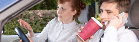 Disappointed woman talking to the car driver, who is drinking coffee
