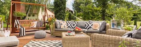 Przestronny taras ze stylowymi meblami ogrodowymi i drewniane huśtawki ogrodowe