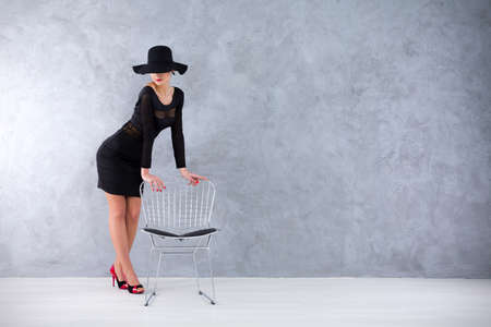 vamp: Alluring slender woman in a black cocktail dress and a sexy hat resting upon a silver diamond chair