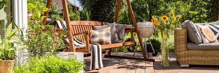 Przytulny dom z drewnianym tarasem w ogrodzie huśtawką i grillem