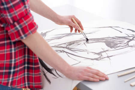 bright paintings: Close-up of an artist painter working on a black and white brush sketch Stock Photo