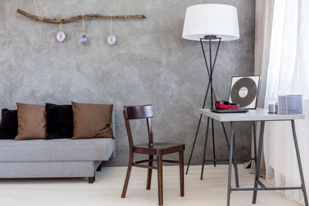 ascetic: Ascetic living room in grey, with a brown vintage chair next to a modern desk top