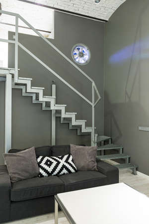 entresol: Shot of a sofa and a staircase in a modern grey apartment Stock Photo