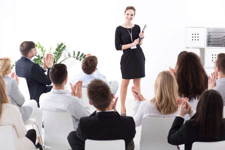 management team: Smiling young manager standing in front of meeting members who are clapping hands at her Stock Photo