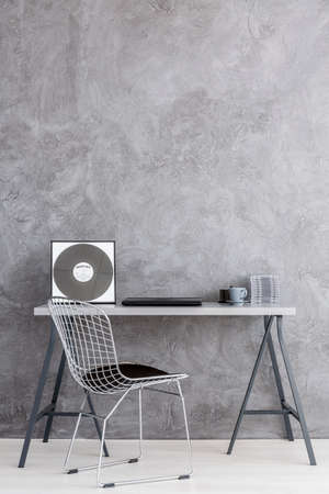 stucco wall: Very minimalistic desk corner in grey, with a diamond chair and a stucco wall Stock Photo