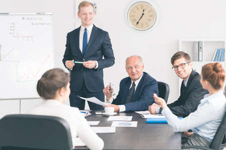commenting: Group of managers of different ages sitting around a table in a bright office and commenting on graphs on a whiteboard