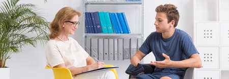 traumatic: Bright interior of therapy center with therapist and her patient Stock Photo
