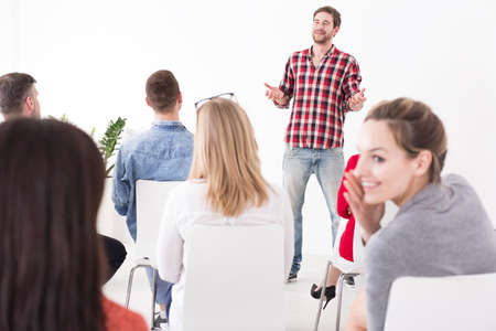 likeable: Likeable young manager holding a presentation while his colleagues are gossiping in the blurry back row