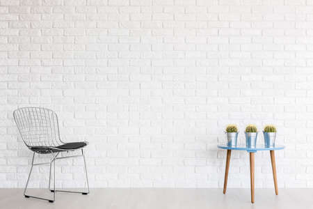 wall design: Metal diamond chair and a blue coffee table with cactuses at a white brick wall