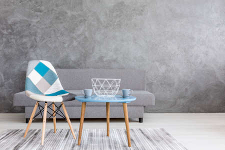 Silla del diseñador del remiendo por una mesa de café azul en un interior minimalista dispuesto en gris
