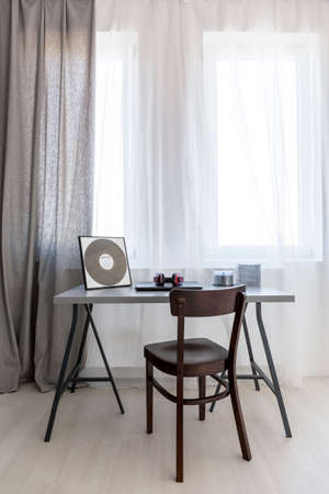 ascetic: Desk top based on trestles and a renovated vintage chair by the window in a modern room