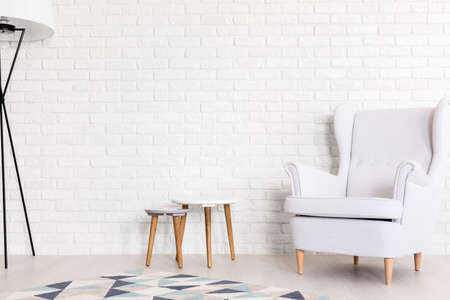 lamp: Very bright shot of white wing chair, set of coffee tables and a floor lamp next to a white brick wall