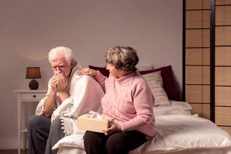 Senior homme assis sur le lit soufflant son nez et sa femme soignante l'appuyant