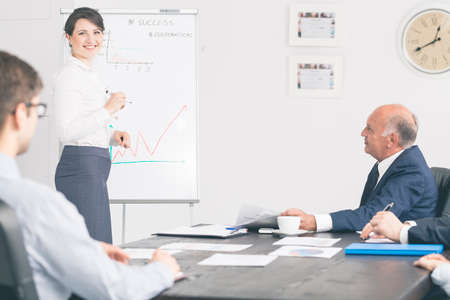 president: Young smiling assistant presenting some figures on a whiteboard in front a senior manager