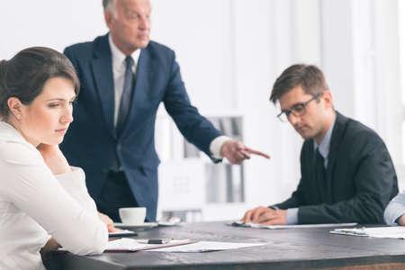 Close-up von einem jungen Büroangestellten zu ihrem Chef zu hören einer ihrer Kollegen kritisieren