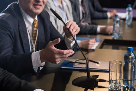 Politician delivering his speech to the microphone during press conference Stock Photo