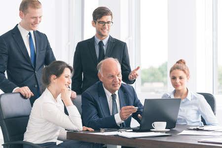 Elegante hogere zakenman die iets op een laptop aan zijn jonge coöperaties Stockfoto