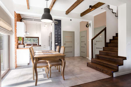 Big and beautiful kitchen with stairs leading up and garden view