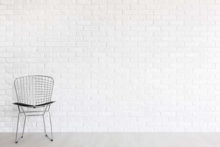 industrial design: Shot of a silver diamond chair by a white brick wall Stock Photo