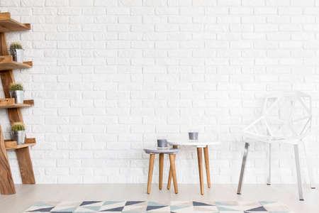 Sedia divanetto bianca, tavolini e ripiano scala in un interno molto luminoso con muro di mattoni bianchi