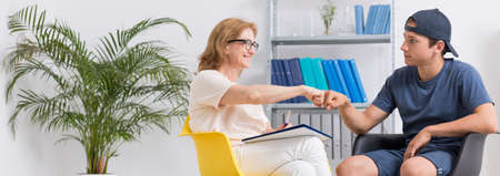 feelings and emotions: Therapy session with the teenager doing fist bump with his psychotherapist