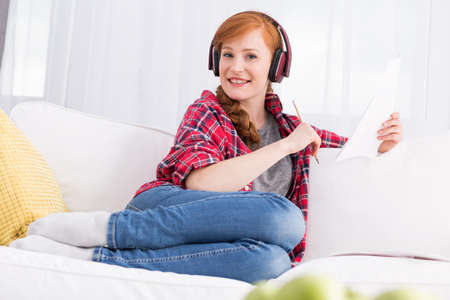 revise: Relaxed young woman in headphones, sitting on a white sofa with some notes in her hand