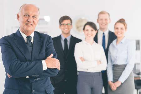Portret van een elegante oudere zakenman met zijn jonge werknemers in de wazige achtergrond