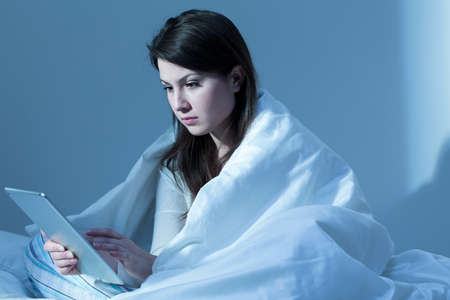 insomniac: Shot of a focused young woman sitting on a bed and using her tablet at night Stock Photo
