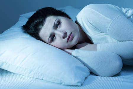 insomniac: Shot of a worried young woman trying to fall asleep Stock Photo