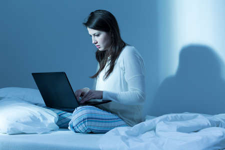 insomniac: Shot of a young brunette woman sitting on a bed and working on her laptop