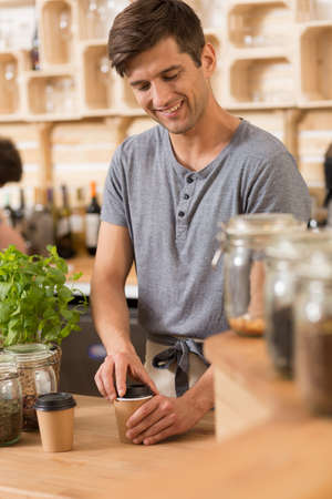 Smiling male barista is preparing a take away cup of coffee