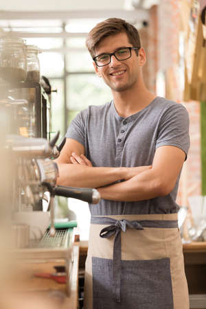 Young confident man is standing and smiling in his coffee shop