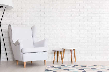 wall design: White upholstered armchair and a set of coffee tables in a white interior with brick wall