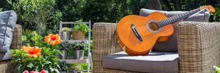home and garden: Closer shot of a guitar located on an armchair in cozy terrace