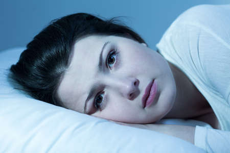 Portrait of a young woman laying on a pillow with her eyes open Stock Photo