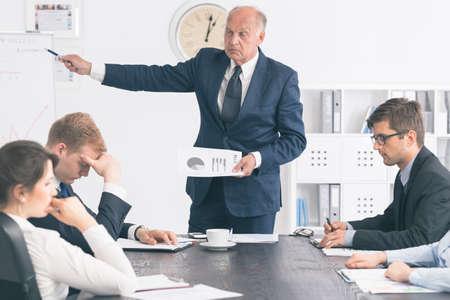 Verärgerter älterer Geschäftsmann einer der Teilnehmer eines Unternehmens Sitzung kritisiert