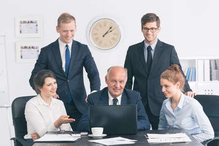 若いサラリーマンのグループがラップトップで働く笑顔上級ビジネスマンの周りに集まった