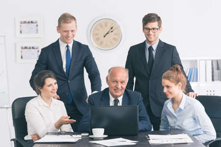 Group of young office workers gathered around a smiling senior businessman working at a laptop