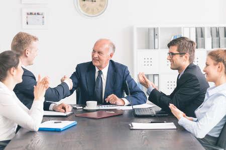 Riunione d'affari ad un grande tavolo, con un anziano uomo d'affari stringe la mano con un più giovane