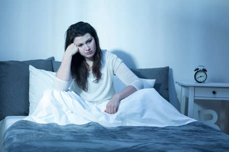 Shot of a resigned young woman sitting on a bed and not being able to fall asleep