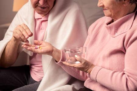 ヘルスケア: 彼女の病気の夫に薬を与えて水のガラスを保持している年配の女性