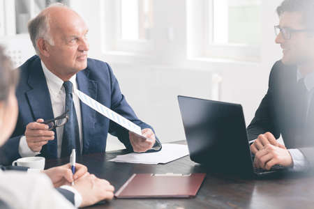 chairman: Close-up of a senior businessman talking to a young employee during a meeting at an office table