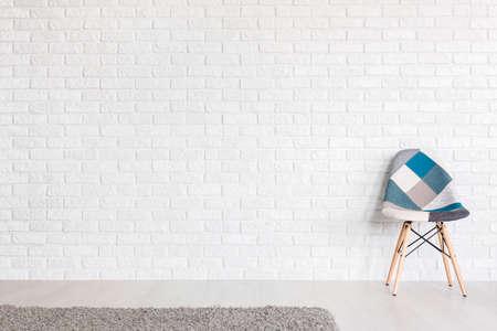 sedia patchwork con colori lievi da un muro di mattoni bianchi